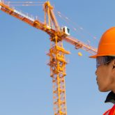 construction worker with crane in the background